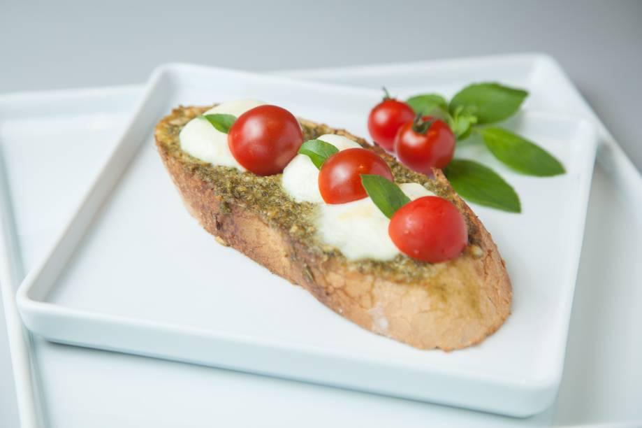 Tostada no filão italiano coberta por alho,molho pesto, tomate-cereja, mussarela debúfala e manjericão
