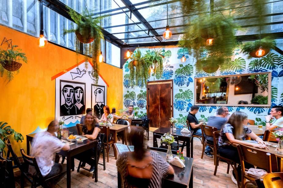 Salão do bar Exquisito!:mistura entre xilogravura, lambe-lambe, quadros e plantas nas mesas, nas paredes e no teto