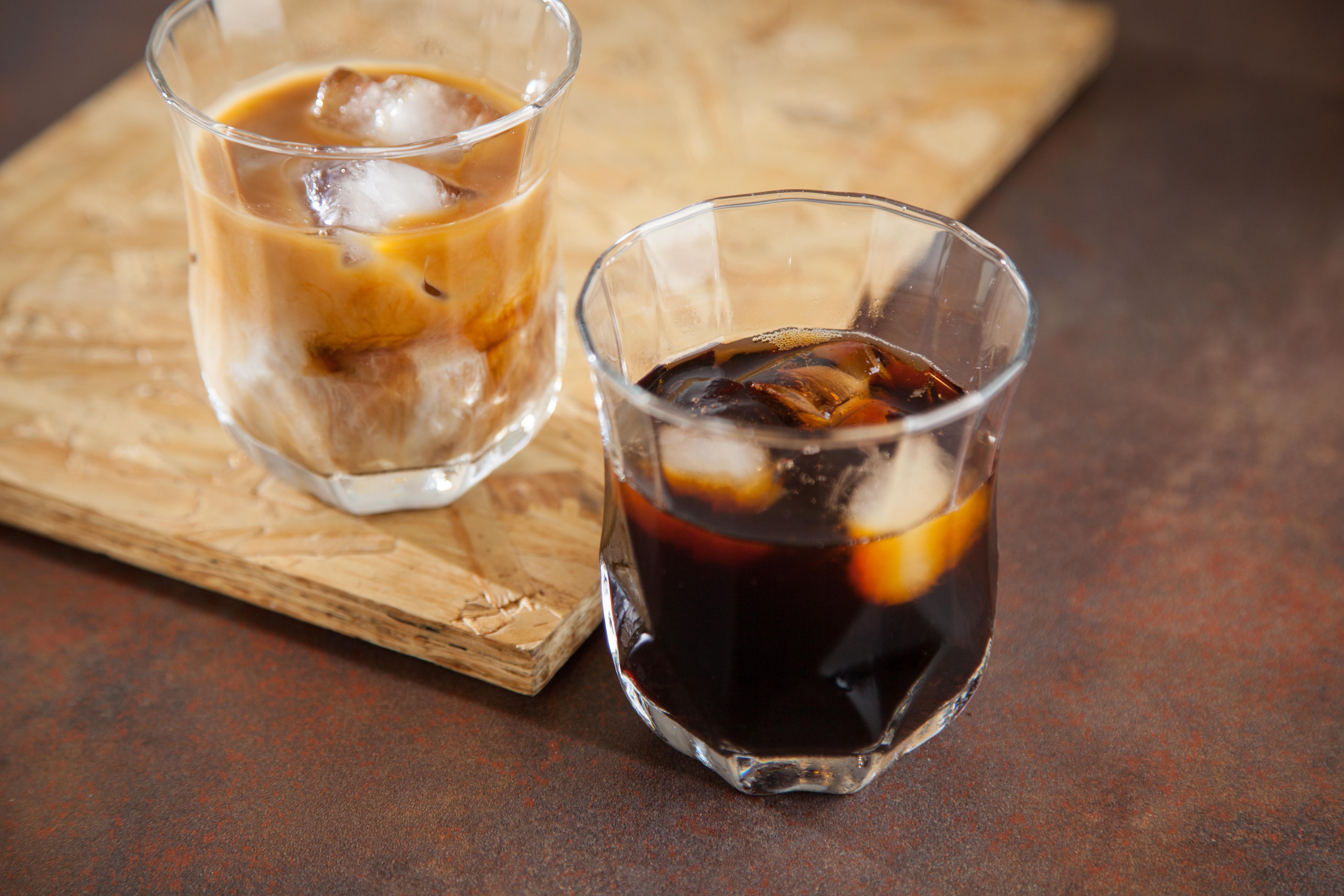 Dois copos de cafés, um à frente escuro e com gelo, o de trás com gelo e leite