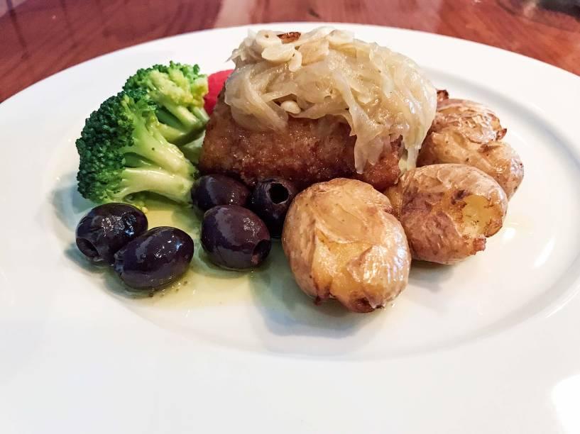 Bacalhau à lagareiro: posta do pescado com cebola dourada, batata ao murro, tomate confit, alho laminado e brócolis verdinho