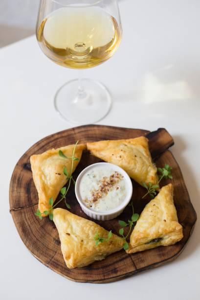 Espanacopita: torta de espinafre vem como um pastelzinho assado, triangular, recheado de queijo feta e crocante de azeitona junto de tzatziki, o pepino em iogurte e alho