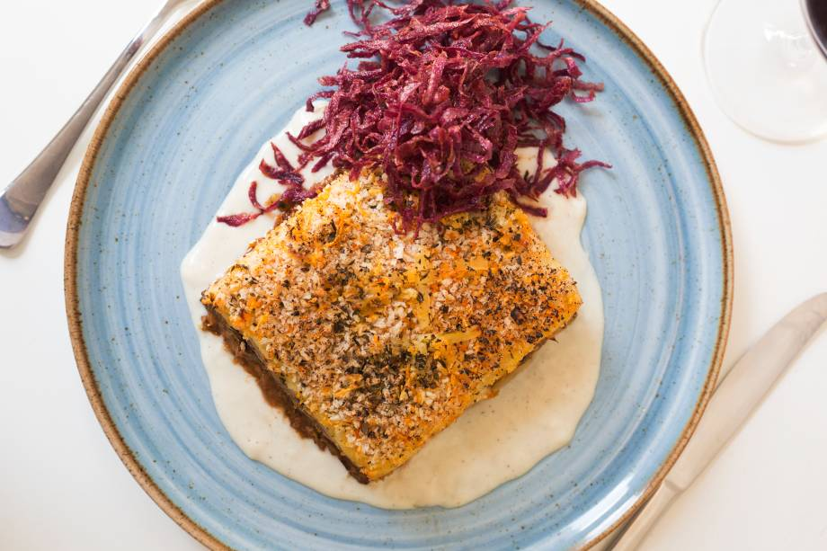 Mussaká: camadas de lâminas de berinjela e batata com carne moída cobertas por creme de queijo de cabra e crocante de batata-doce palha