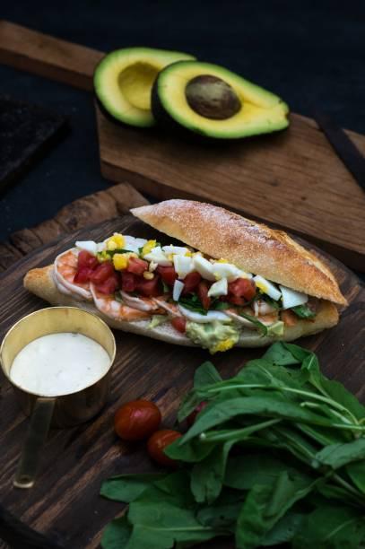 Sanduíche com camarão, abacate, maionese de ovos cozidos, tomate e rúcula