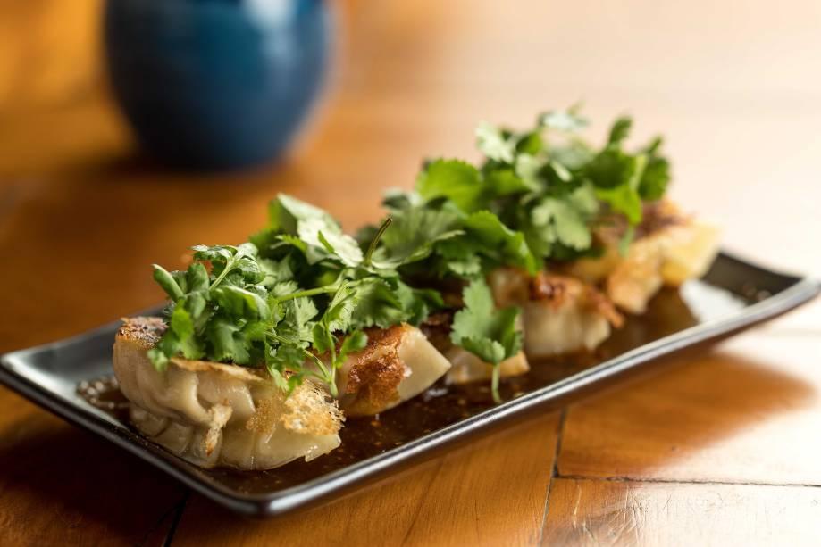 Porção de guioza: recheada de porco, vem coberto de folhas de coentro e molho de pimenta, shoyu e vinagre