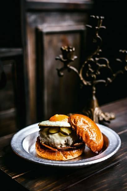 Hambúrguer sertó: queijo meia-cura, pepino em conserva, maionese, bacon e ovo frito de gema mole no brioche