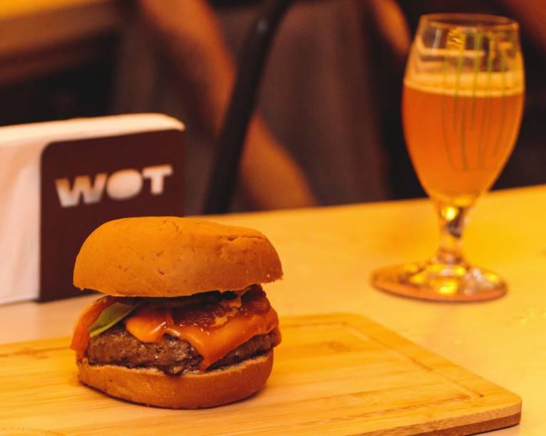 Hambúrguer e cerveja: sanduíche com queijo do tipo cheddar, geleia de bacon, picles de maxixe, rúcula e maionese no pão de cerveja stout e chope IPA