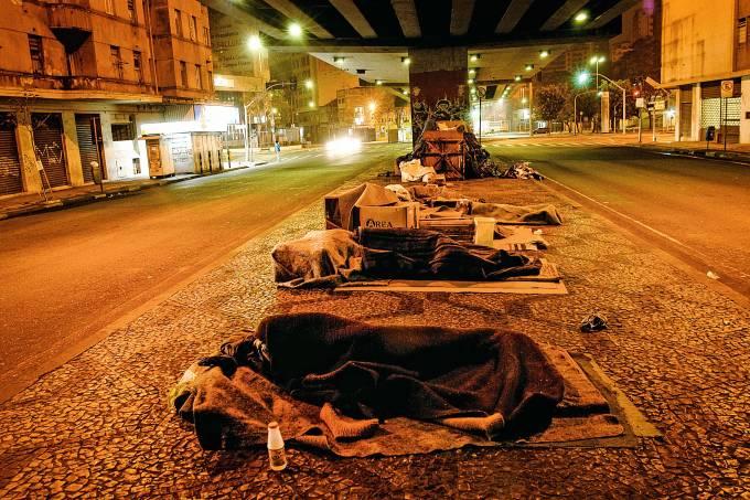 Moradores de rua dormindo embaixo do Minhocão, à noite, no centro da cidade.