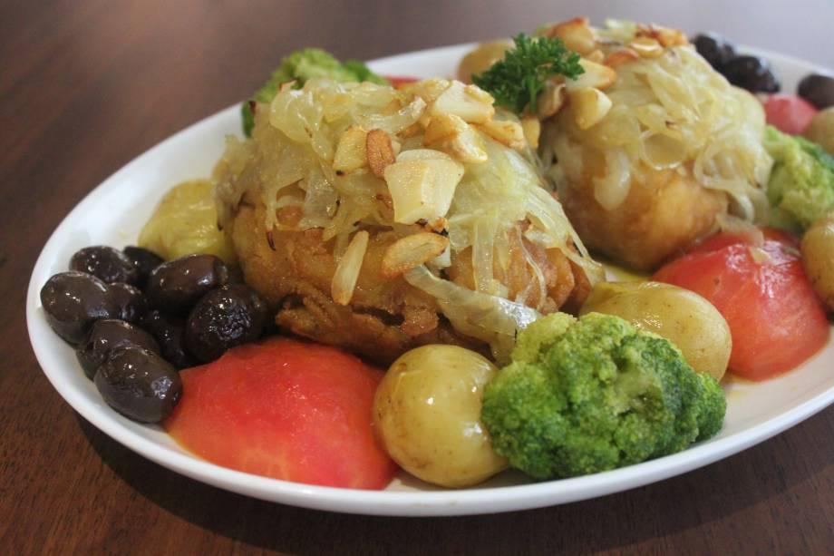 Bacalhau à lagareiro: posta do peixe assada e guarnecida de alho, batatinha ao murro, brócolis, tomate e azeitona