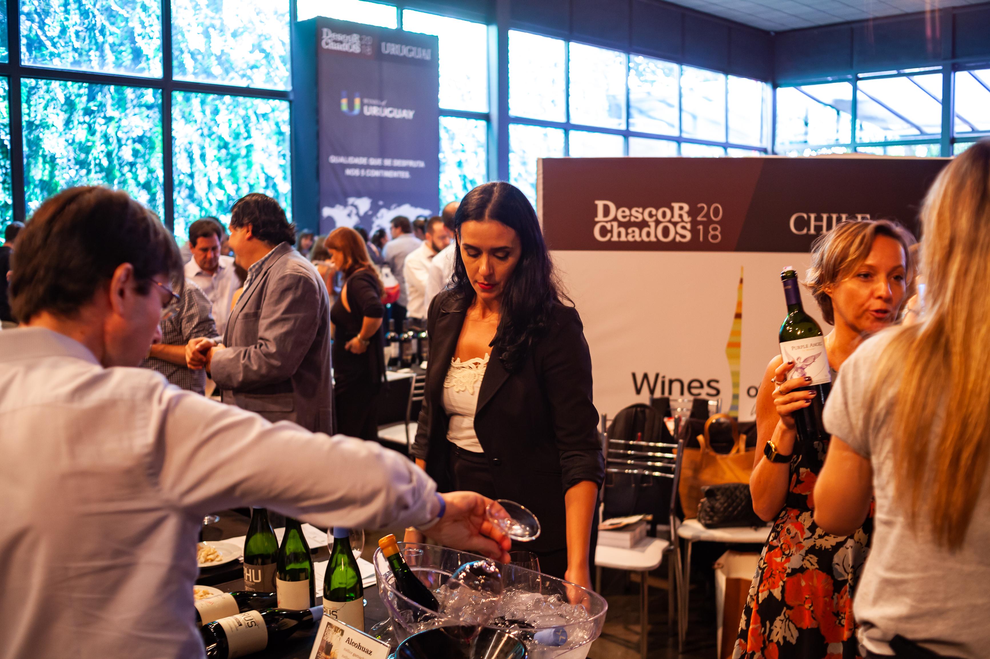 Pessoas em pé ao redor de mesas onde são servidos vinhos
