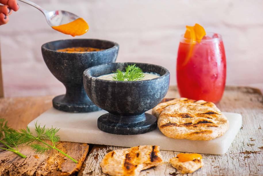 Dupla de tirokafteri e tzatziki: pastas de queijo feta com pimentão e de pepino com iogurte e pão pita