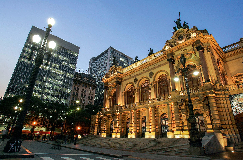 A imagem mostra a faixada do Teatro Municipal, iluminada, em um fim de tarde com o céu parcialmente escuro.