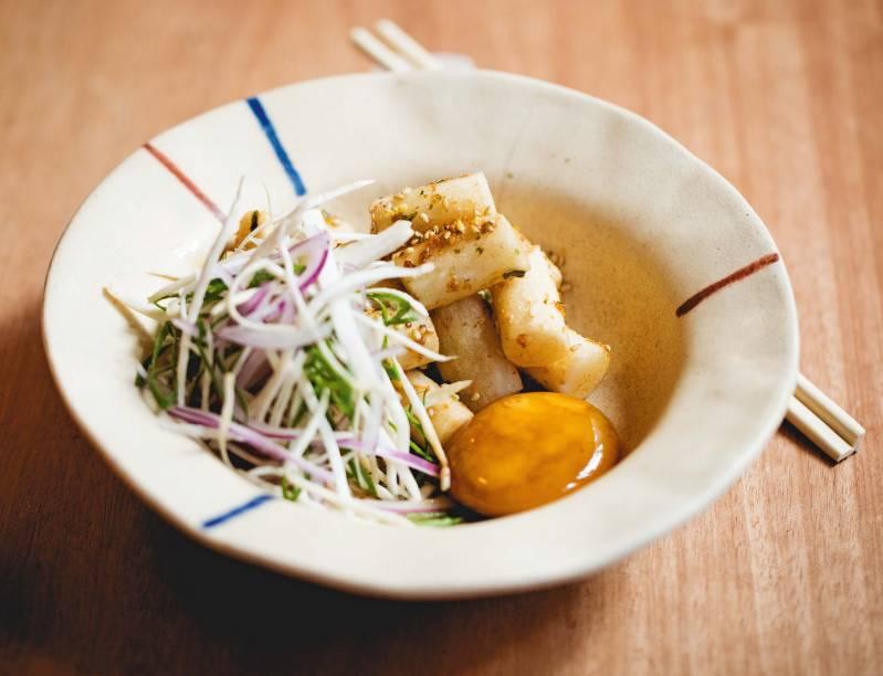 Topoki: cilindros de massa de arroz grelhados e crocantes, servidos com gema de ovo curada, cogumelo, cebola-roxa e molho de saquê mirin