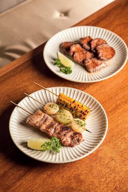Petiscos que saem da churrasqueira: língua, milho, cebola e barriga de porco