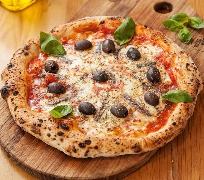 Napolitana: molho de tomate, mussarela, azeitona preta e folhas de manjericão