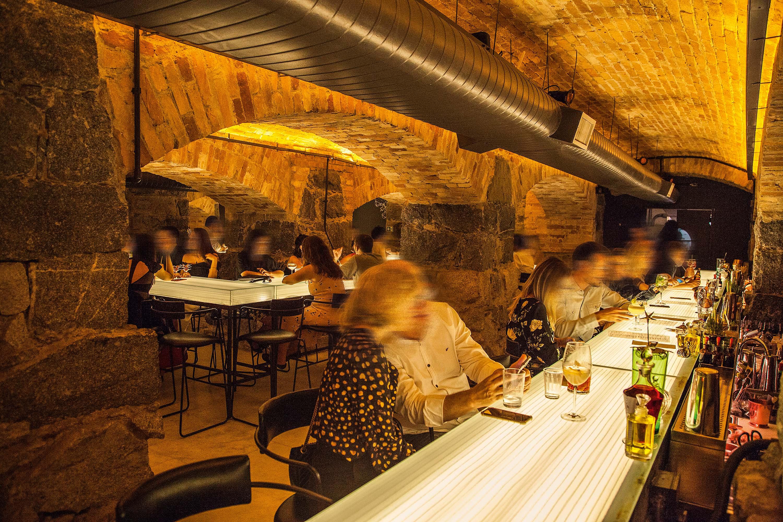 Balcão de bar iluminado com pessoa sentadas mais mesas ao fundo