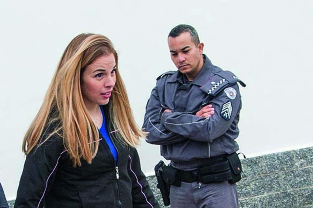 A imagem mostra Suzane sendo encarada por policial