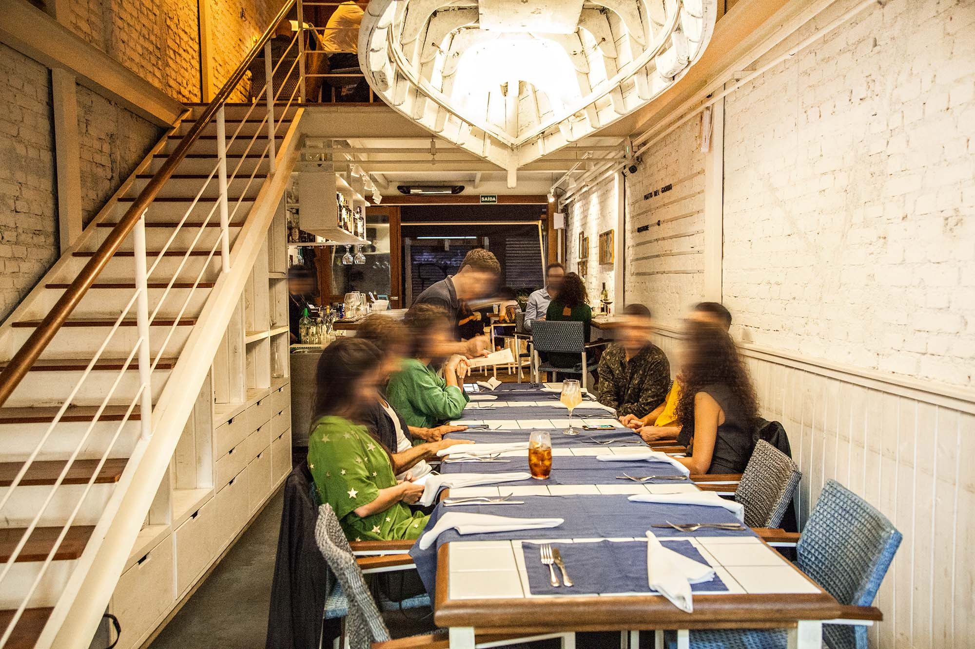Parte térrea do salão do restaurante Lido Amici di Amici com pessoas sentadas em uma mesa coletiva