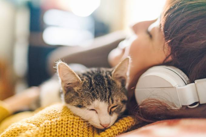 Relaxed girl with cat listening to music