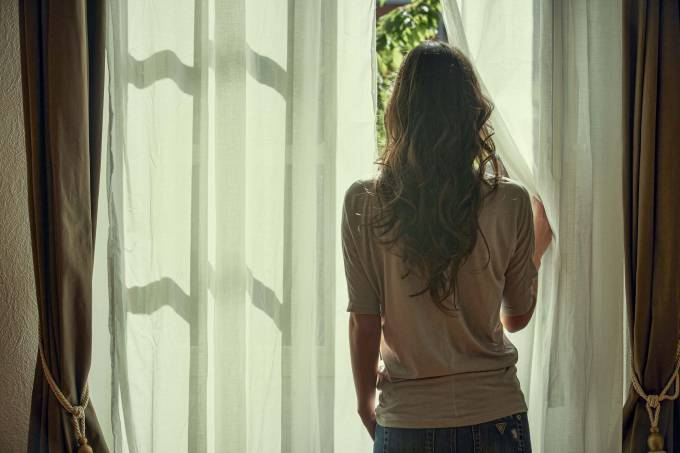 Young woman peeking out from net curtains