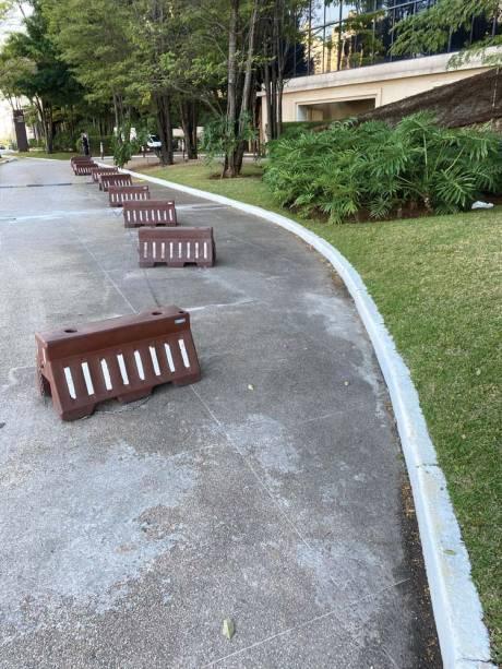 """O Parque Cidade Jardim: paredão de garagens para a rua, onde balizas improvisam """"calçada"""" para o pedestre, que não tem espaço nem na rampa"""