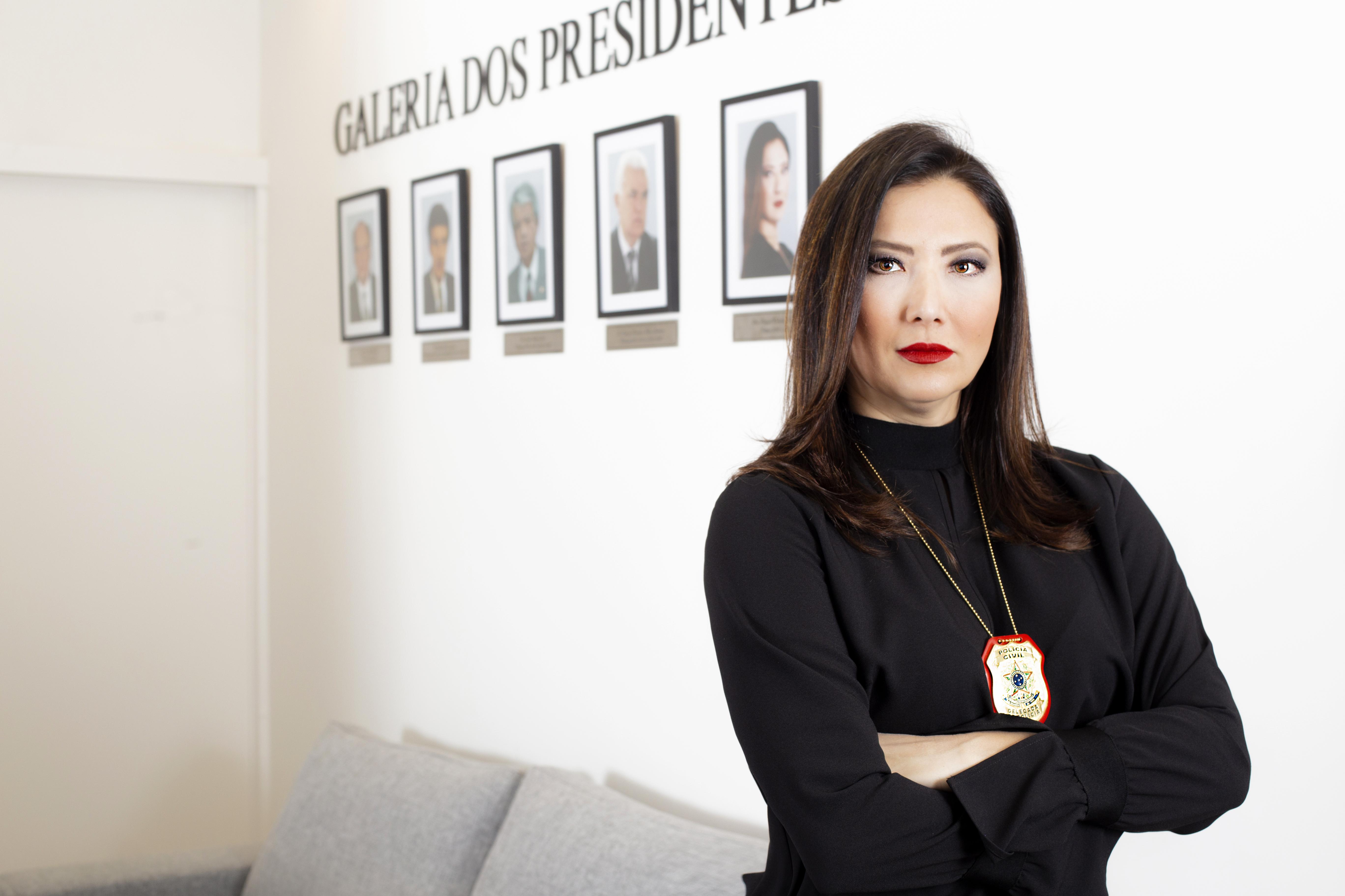Raquel Gallinati, presidente do Sindpesp, posa ao lado dos retratos dos presidentes anteriores vestindo um suéter preto e batom vermelho.