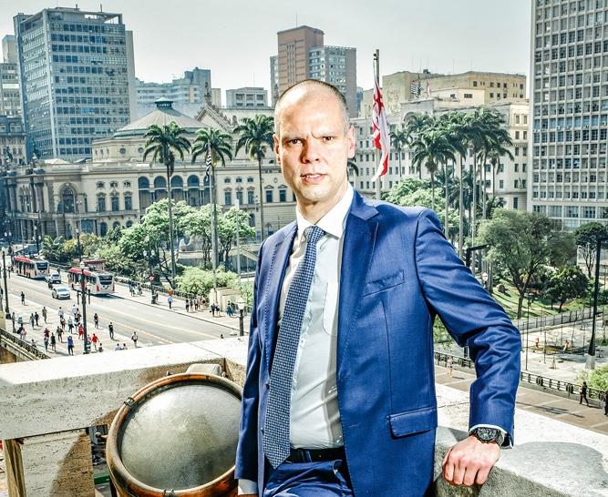 Imagem de Bruno Covas posando para foto com a cidade de SP ao fundo