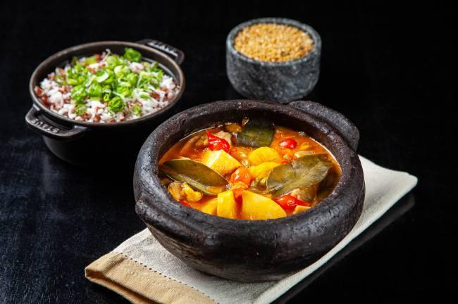 Superfície preta com panela de moqueca ao centro para a esquerda, panelinha de ferro com arroz no fundo à esquerda e cumbuca de pedra com farofa no fundo à direita.