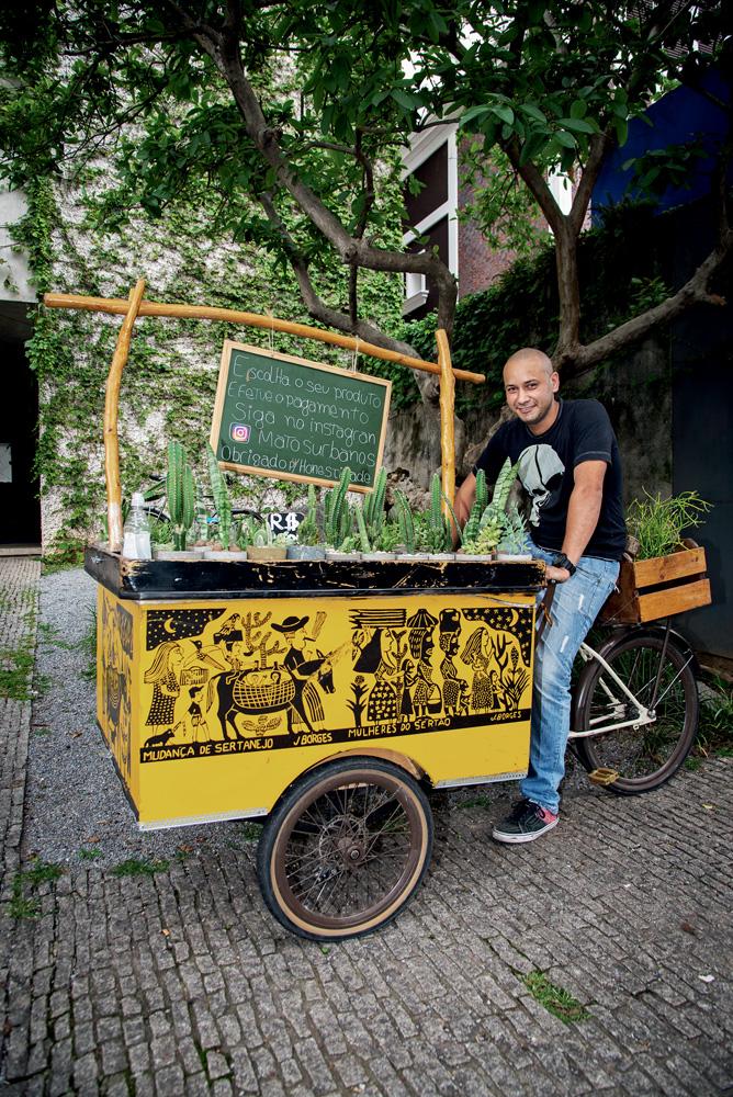 Israel Joaquim posa sentado em bicicleta com bancada amarela, mini-lousa com nome