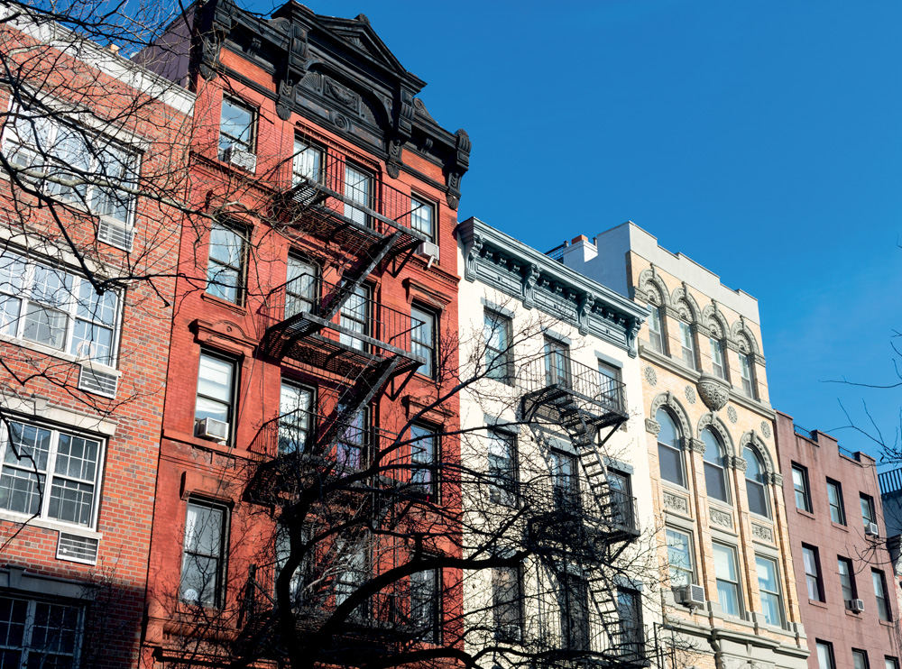 A row of colorful old brick buildings with fire escapes in the East Village of New York City
