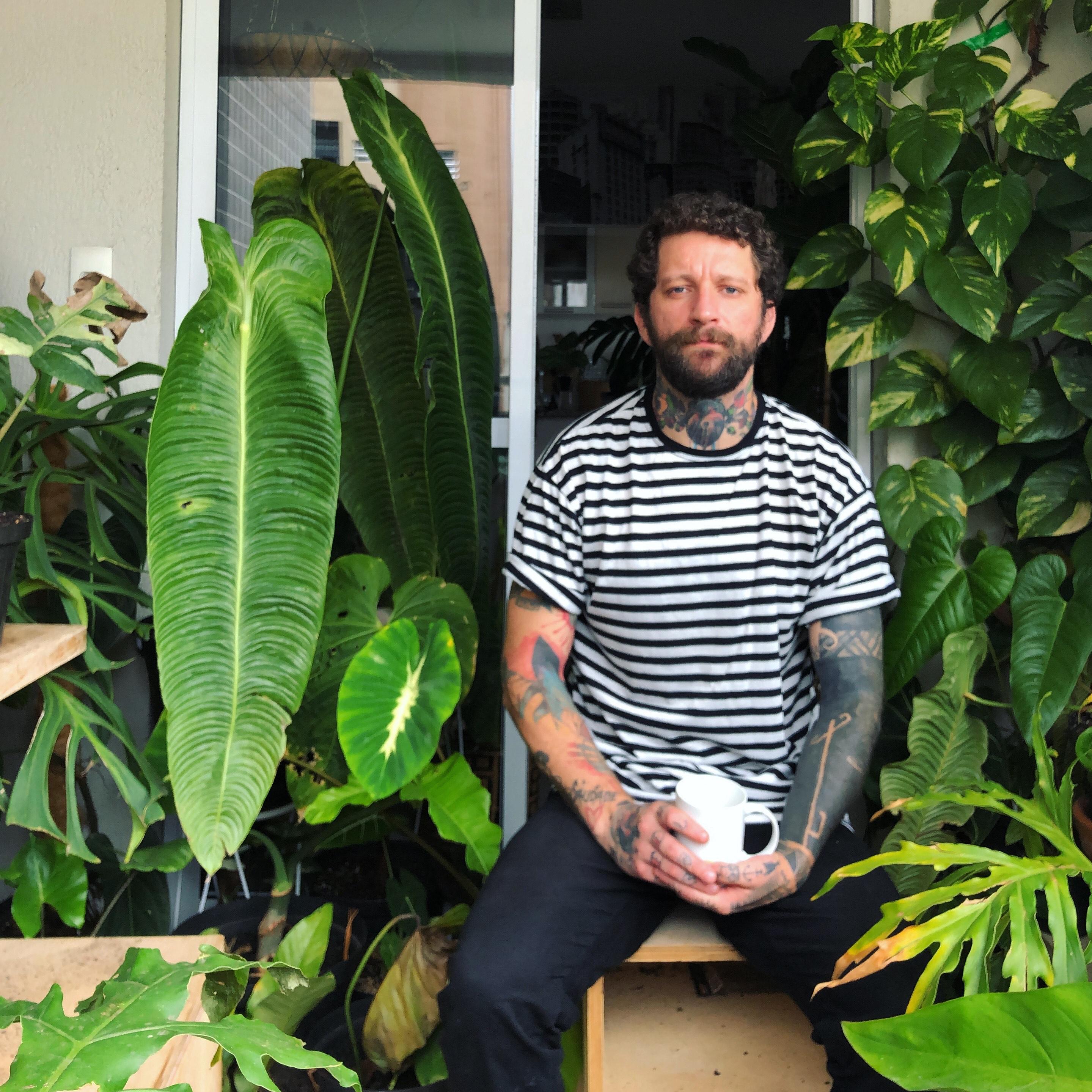O barista Taniel segura uma caneca sentado na varanda de casa. Veste jeans escuras e uma camiseta com listras brancas e pretas. Ao redor, plantas com folhas verdes ocupam todo o espaço.