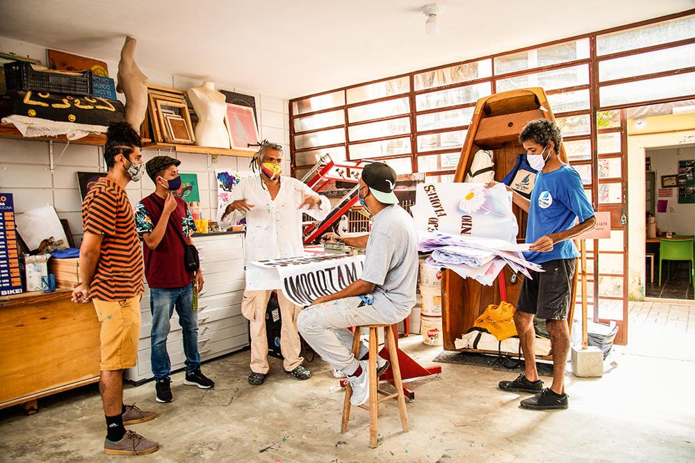 Mauro Neri com outras pessoas dentro de um ateliê. No centro, uma mesa com cartazes empilhados
