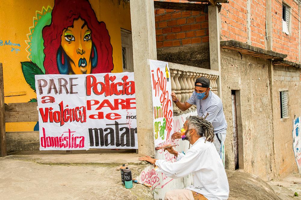 Neri pintando cartazes junto com alunos do projeto Imargem