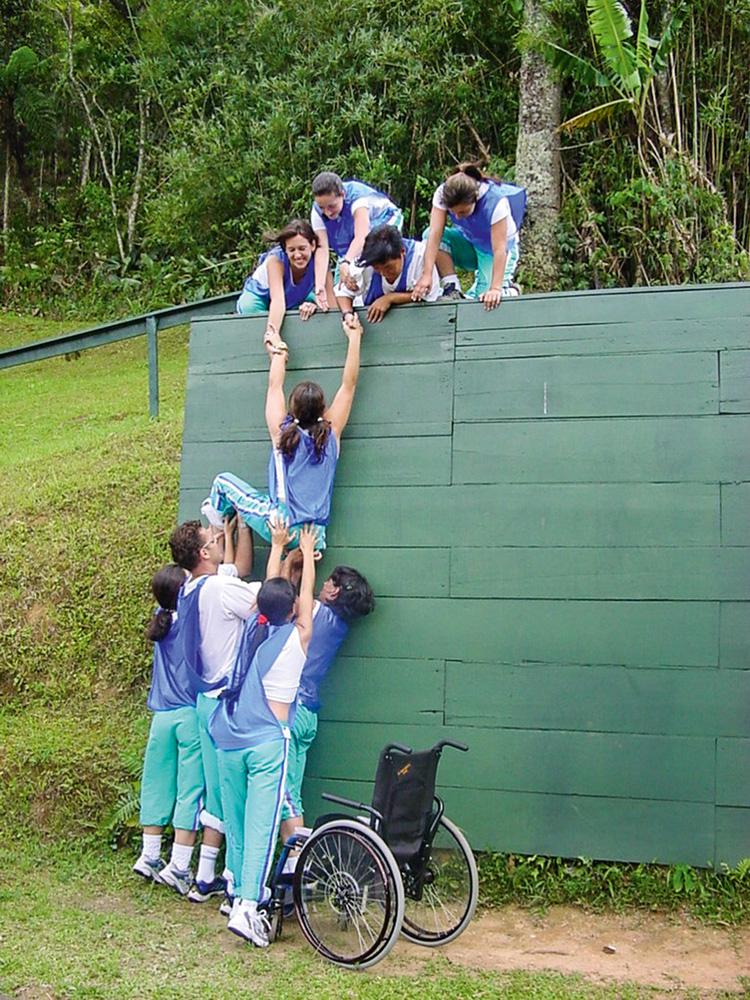 Carol treinando. Enquanto é empurrada por colegas, ela tenta alcançar a parte de cima de um muro verde, com auxílio de outras pessoas já na parte de cima