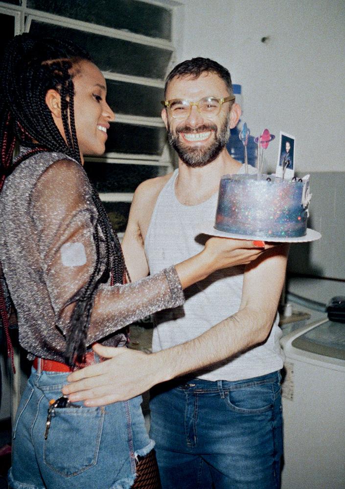 Bárbara segura um bolo de aniversário quando Leo a abraça