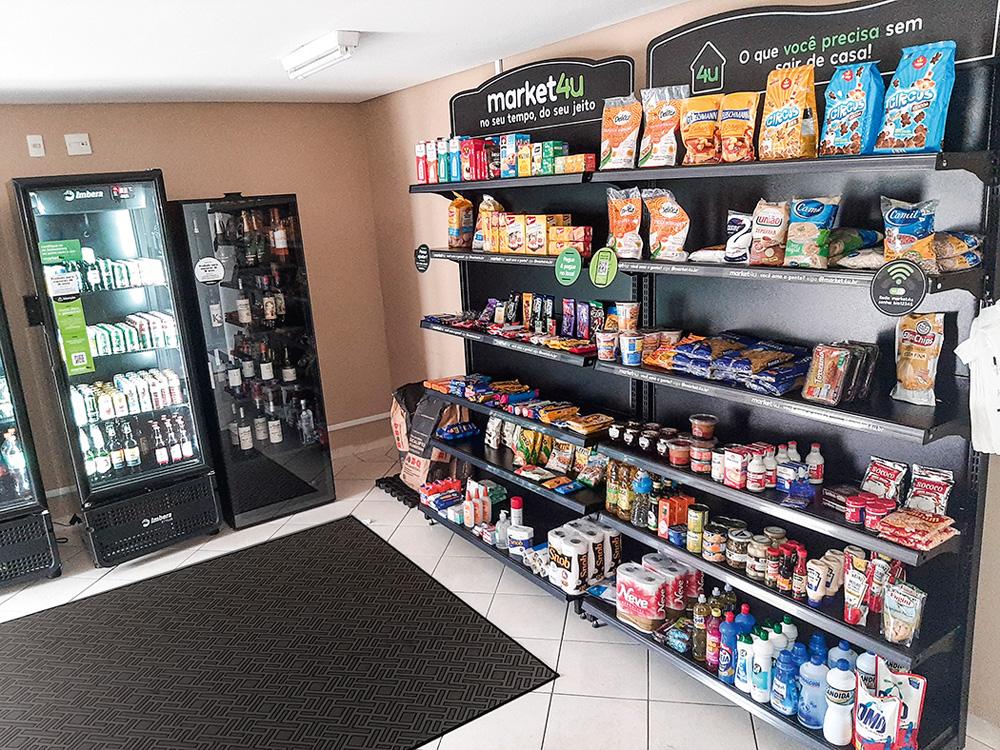 Prateleiras cheia de produtos e geladeira com bebidas.