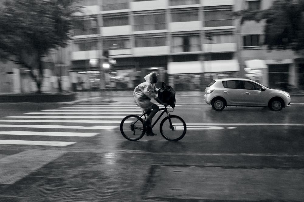 Homem andando em uma bicicleta no meio da rua durante a chuva. Preto e branco.