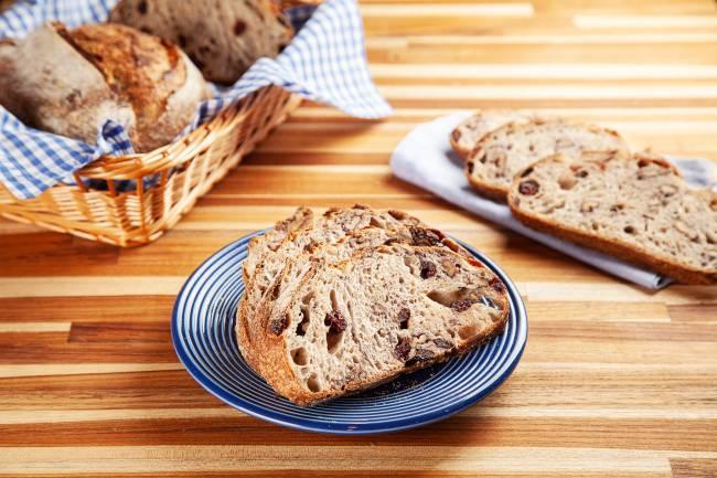 Fatias de pão sobre prato azul ao centro, em cima de mesa de madeira. No canto superior esquerdo, cesta de palha com pães e à direita, guardanapo de pano dobrado com três fatias de pão.