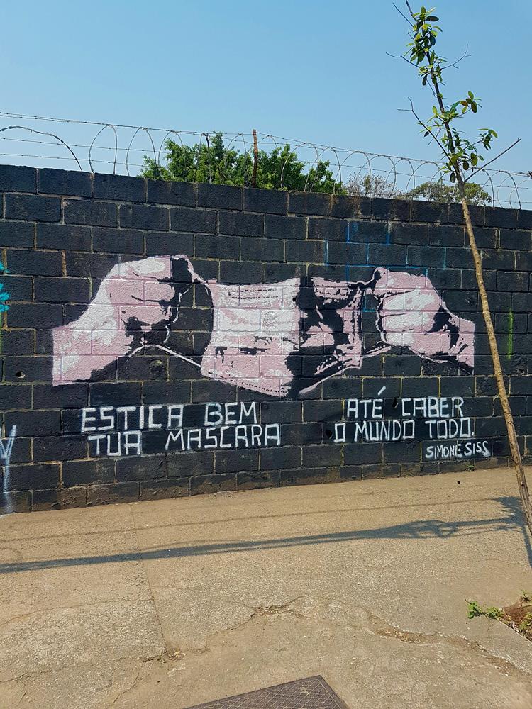 Mural em que duas mão mantém uma máscara estendida. Em baixo da imagem está escrito
