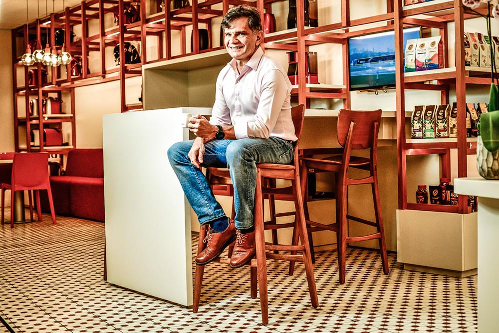 Dono do café 3Corações sentado em um banquinho