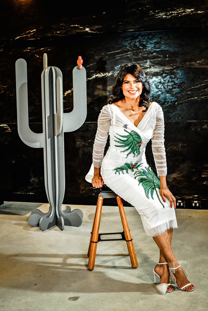 Renata França senta em um banquinho com um cacto artístico do lado
