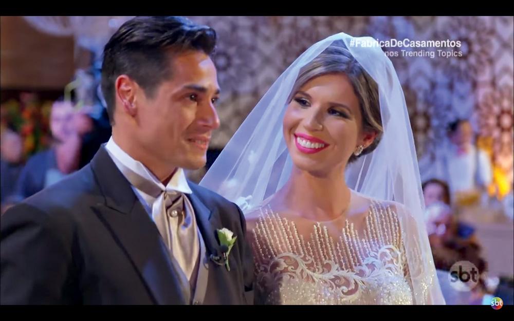 Rejane vestida de noiva, olha apaixonadamente para Giovanni, de terno
