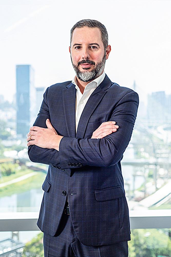 Thiago Castro, diretor executivo da Tegra, posa de braços cruzados e terno cinza-escuro.