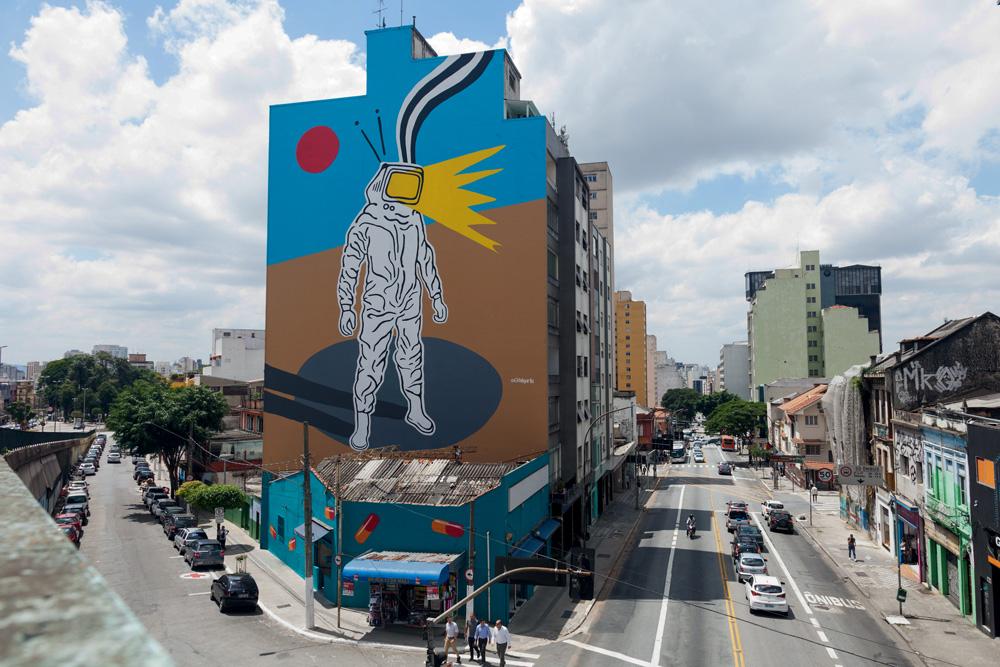 Mural feito em um prédio. Um astronauta com cabeça de televisão.