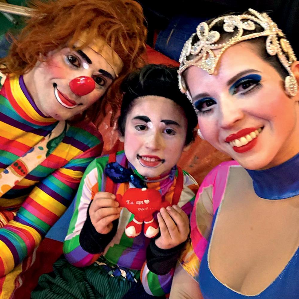 Ícaro sorri com os pais, Rejane e Giovanni. Todos estão maquiados e com roupas de circo