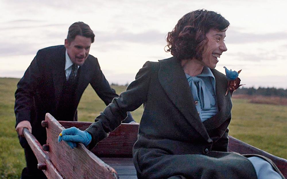 Maudie sendo empurrada, rindo, em uma carroça
