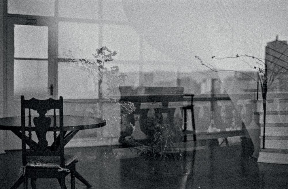 Uma espécie de sala de estar com a imagem meio borrada por um reflexo de outra sala por cima, tudo em preto e branco