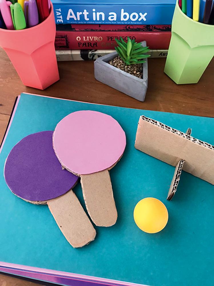 Duas raquetes e uma mesa de pingue-pongue pequena feitas de materiais de papelaria.