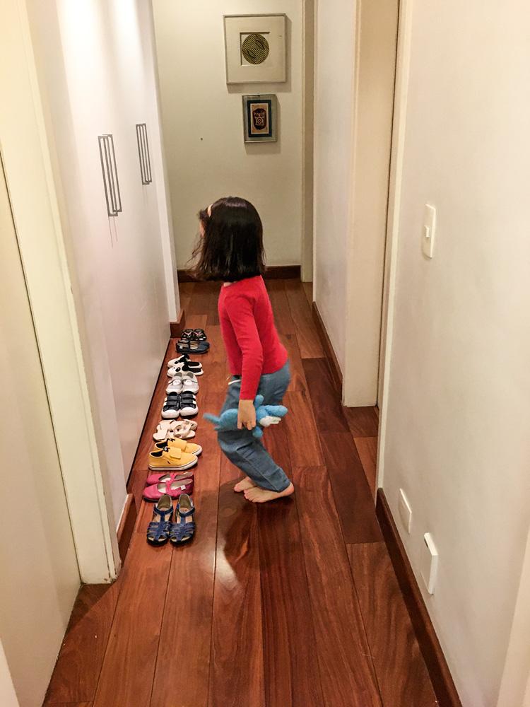 Um corredor com uma criança em frente a uma fila de sapatos