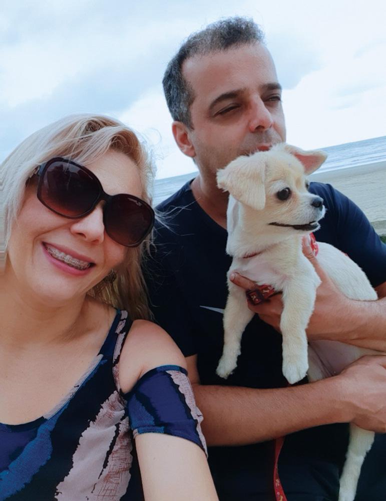 Telma e Clodoaldo passeando na praia com uma cachorrinha no bolo