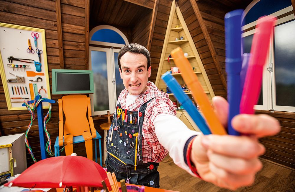 O ator Daniel Warren com canetas na mão e um macacão artístico
